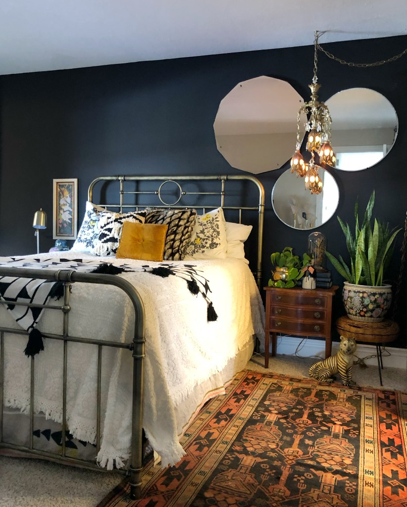 An Eclectic '70s Home Filled With Vintage Finds - Jenasie Earl | Dark decor bedroom styled with vintage mirrors and lighting to create an asymmetrical arrangement to create more interest.