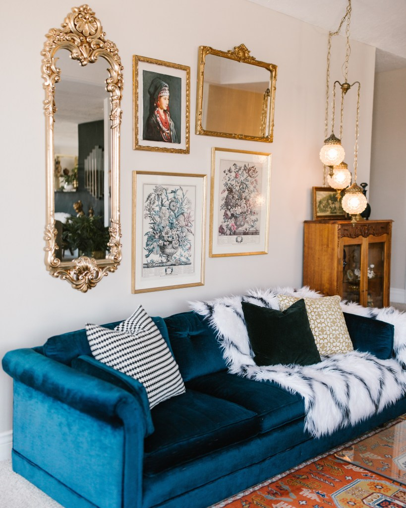 An Eclectic '70s Home Filled With Vintage Finds - Jenasie Earl - Vintage finds include this cobalt velvet sofa, swag lighting, mirrors and artwork.