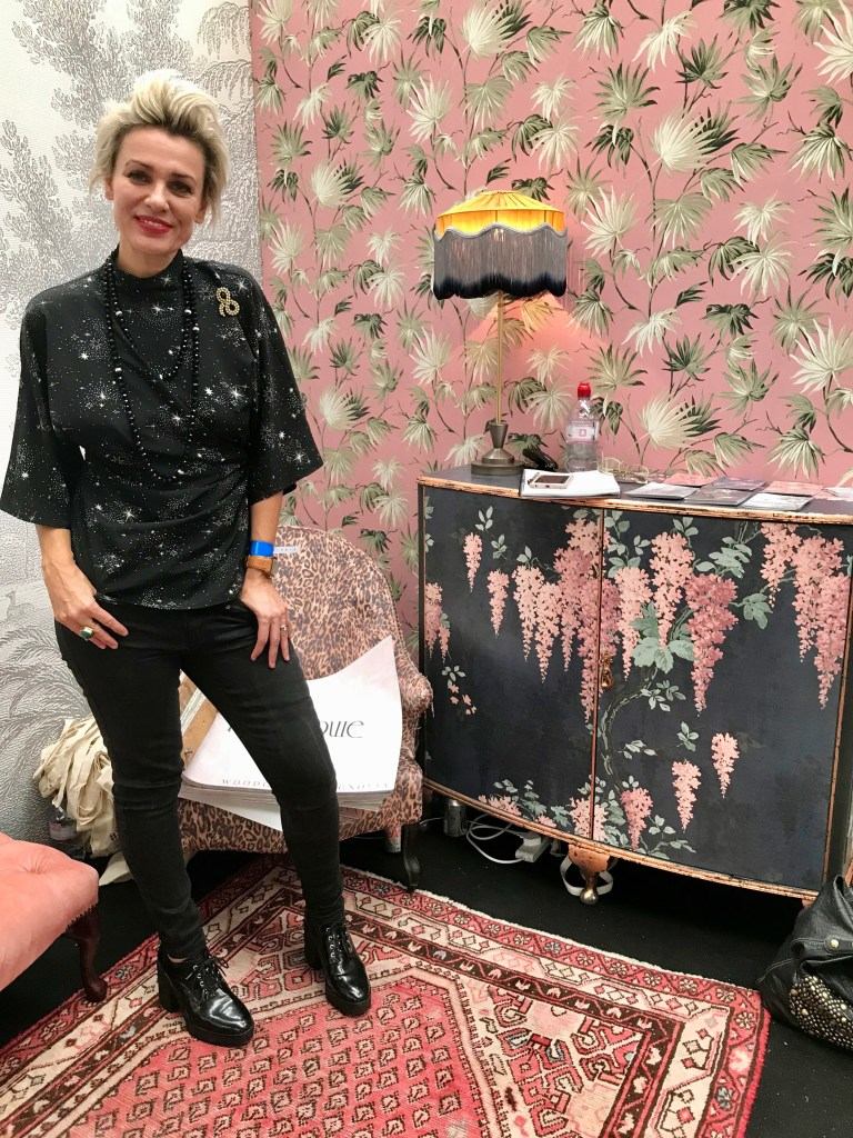 The Unique & Glamorous Maximalist Home of Sarah Parmenter Upcyclist Extraordinaire​ | Sarah at the London Design Fair representing Pearl Lowe wallpaper collection including one of her upcycled furniture designs.
