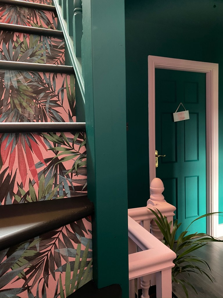 Bold botanical wallpaper and colour blocking in pink and green have been used to create statement stairs and landings. Colour & Pattern Filled Eclectic Home - Saara McLoughlin
