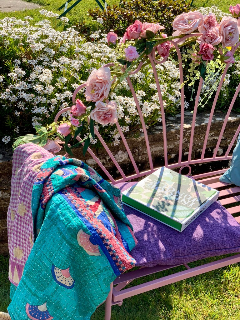 Easy Styling Tips For Your Garden Seating Areas - Faux rose garland adds detail to a garden bench