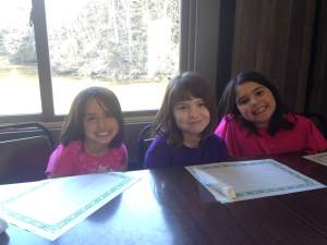 Gigi, Bella and Leah ready for lunch at Bluff Lake Catfish Farm with the lake and it's waterfall behind them.