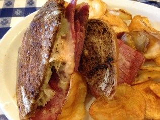 Traditional Reuben Sandwich. Tender pastrami with Swiss cheese, house made 1000 Island dressing, Amana style sauerkraut on marble rye with homemade potato chips.