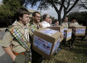 FILE - In this Feb. 4, 2013 file photo, James Oliver, left, hugs his brother and fellow Eagle Scout, Will Oliver, who is gay, as Will and other supporters carry four boxes filled with a petition to end the ban on gay scouts and leaders in front of the Boy Scouts of America headquarters in Dallas, Texas. Under pressure over its long-standing ban on gays, the Boys Scouts of America is proposing to lift the ban for youth members but continue to exclude gays as adult leaders. The Scouts announced Friday, April 19, 2013 that the proposal would be submitted to the roughly 1,400 voting members of its National Council at a meeting in Texas the week of May 20, 2013. Tony Gutierrez, File — AP Photo