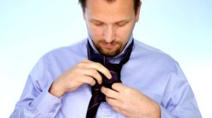stock-footage-young-businessman-tying-necktie-timelapse