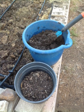 A bucket of clay and a pot of beautiful, organic compost