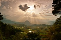 16: Shafts of sunlight filter through the heart-shaped clouds and descend on Mt. Clitoris (officially Mt. Mugaw) in Tadian, Mountain Province, which towers over rice terraces.