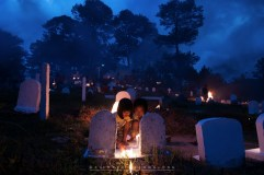 """28: Two youngsters play with candle fire at tomb inAnglican cemetery in Sagada, Mountain Province, where the local town people gather for """"Panag-apoy"""" (to make fire) at dusk on Thursday, All Saints' Day. Combining Filipino practices with Anglican church rites, the ritual is intended to give warmth to the souls of the departed."""