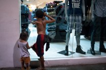 LONGING FOR NEW CLOTHES. Young street children peaks inside the fashion area of a shopping mall in Metro Manila, Philippines.