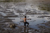 A young boy walks through thick sludge and left over waters of the man-made lake of Burnham Park in Baguio City, Philippines, as it's being drained for rehabilitation and cleaning.