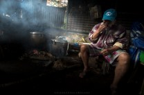 Men who helped the clearing of a landslide area in a community in Baguio City tends a batch of dog-meat being cooked in a make-shift kitchen as they have a drinking session. Dog meat is a popular dish in many parts of Northern Luzon in the Philippines.