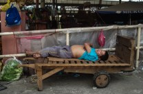 "A ""komboy"" (baggage man) takes a nap after delivering vegetable products along the public market in Baguio City."