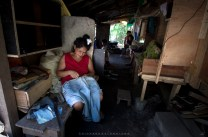 A woman repairs her husband's jeans turned shorts inside their makeshift house at the Philex mines in Benguet.