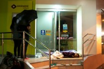 Street children from the southern Philippines sleeps at an entrance of a bank in Baguio City while a couple are seen withdrawing some cash at the bank's ATM.