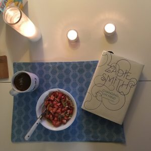 Breakfast layout on a table with a book and candles