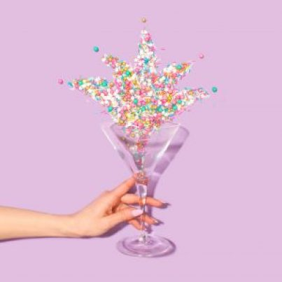 Woman's hand holding a martini glass with confetti spilling out