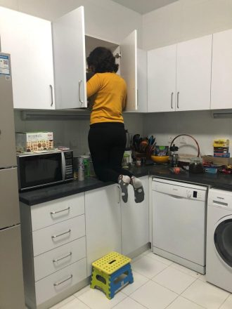 Woman on her knees on a countertop cleaning out her cupboards.