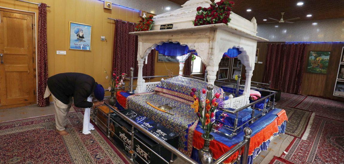 A lone devotee prays at a Gurdawar in Srinagar on Monday…