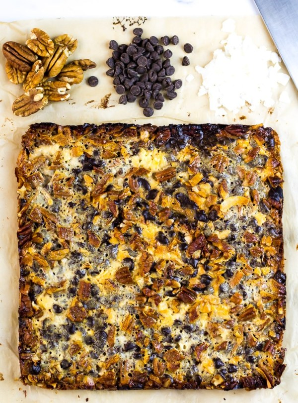 Keto Magic Bars on cutting board with chocolate chips, pecans and coconut