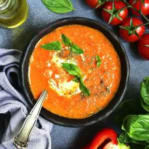 Tomato soup in a black bowl over dark grey slate or stone background.Top view.