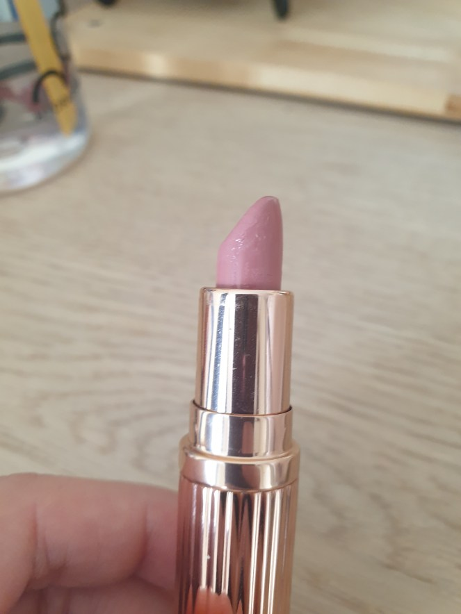 Make up product - Pastel pink lipstick in gold packaging