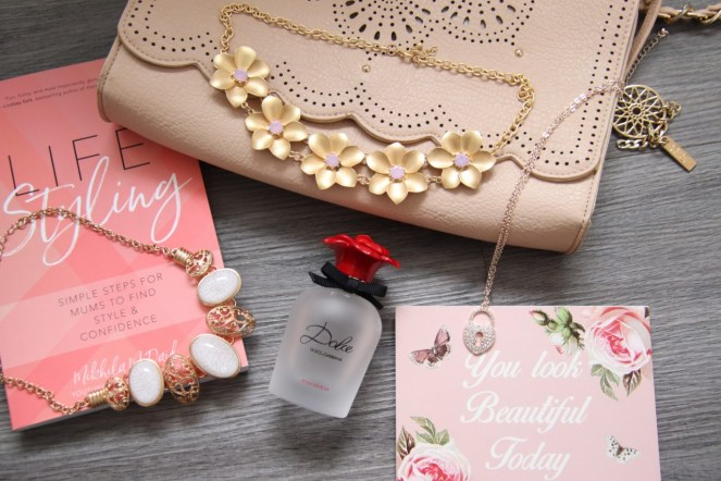 Flat lay photo containing 3 necklaces mentioned within the post, a bottle of Dolce rose perfume, pink book and floral sign. All laid on a cream handbag
