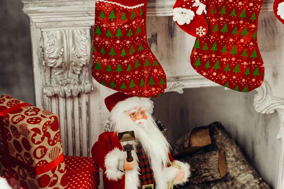 santa claus figurine standing near fireplace