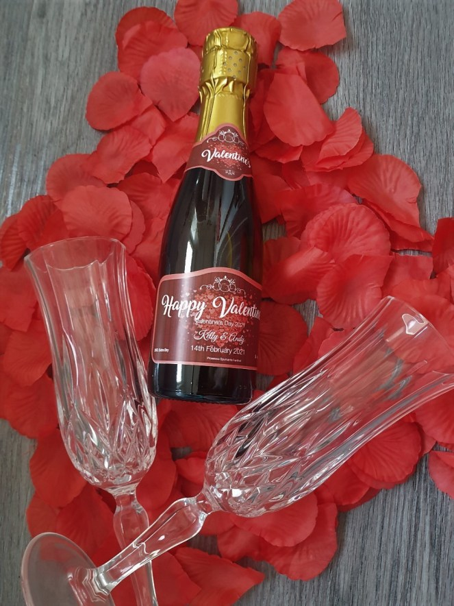 Valentine's gift idea showing Say It With Champers personalised bottle with two crystal flutes on a bed of red rose petals.