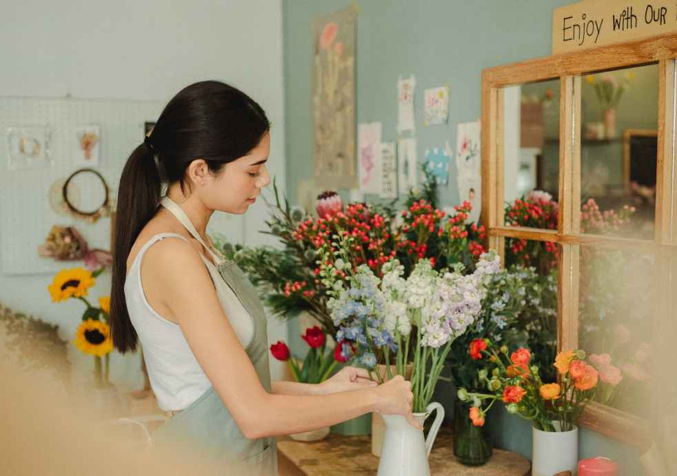woman preparing floral bouquet in floral shop