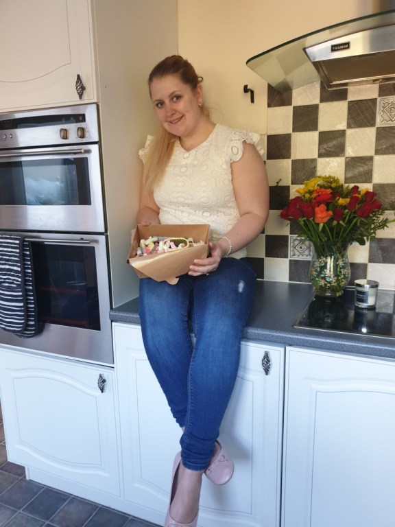 Blonde female sat on kitchen worktop with a box of Panda Sweets Pick N Mix