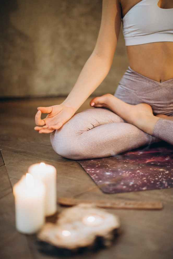 meditating with candles and incense with sustainable yoga mat