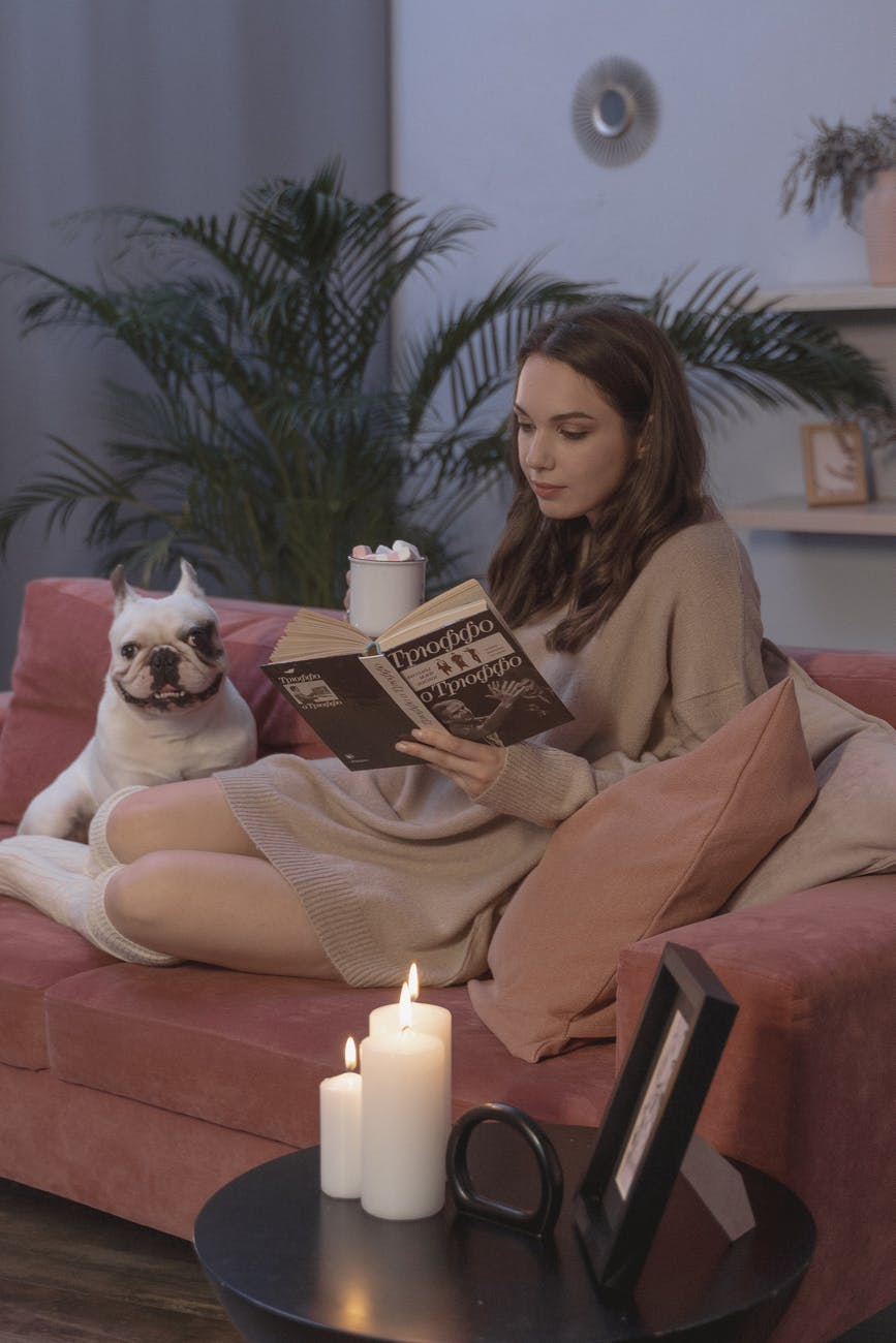 woman sitting on couch while reading a book