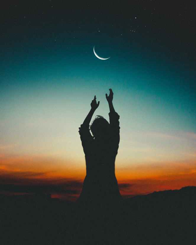 silhouette of woman reaching the moon