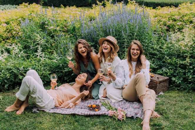 women sitting on green grass field having a catch up.