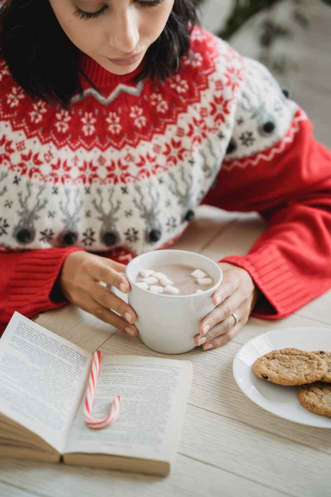 crop woman enjoying hot chocolate and reading book at table during christmas for Calm By The Christmas Tree By Katie Burton post.
