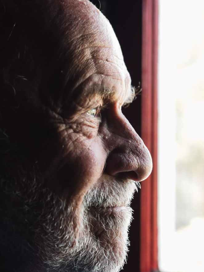 man staring out of window for how to spot the early signs of dementia post.