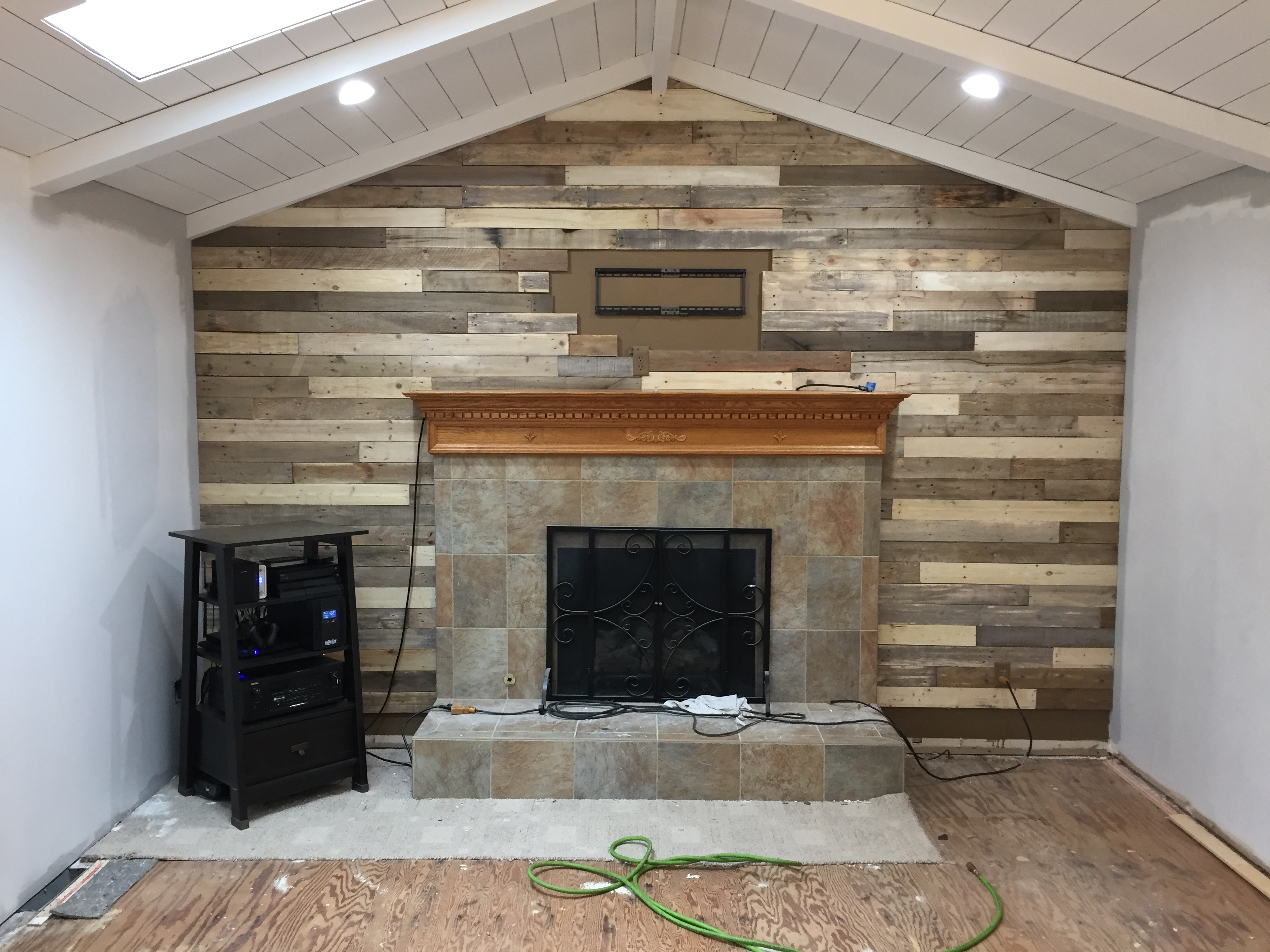 Building wood pallet wall and painting fireplace mantel & tile surround