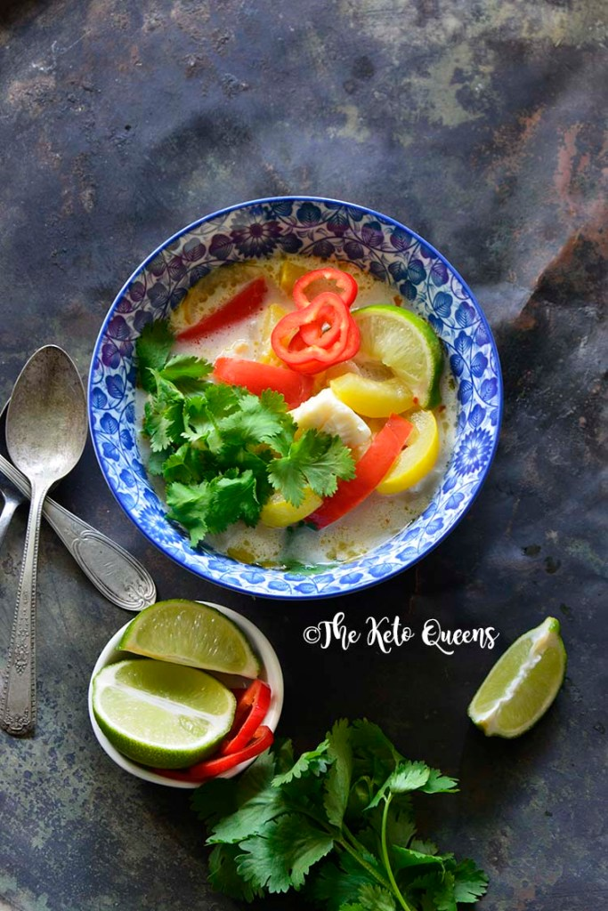 Vertical image of a bowl of thai coconut curry with red bell peppers and yellow squash.