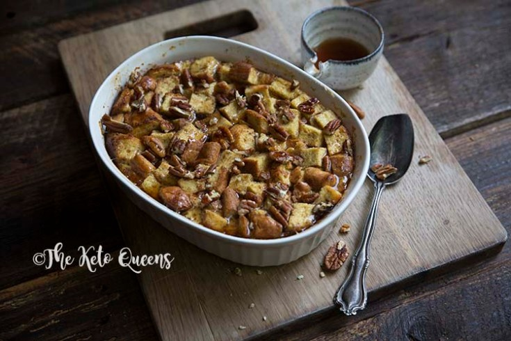 zoomed out horizontal image of maple pecan french toast casserole in a white casserole dish, with a spoon and low carb syrup on a wood background