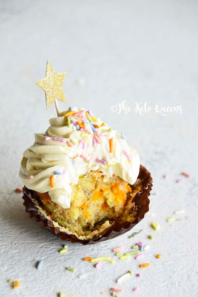 vertical image of a keto cupcake - vanilla cupcake with white chocolate buttercream frosting with sprinkles and a star with a bite taken out of it