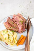 vertical image of corned beef, cabbage and carrots on a white plate with rose-colored fork and knee with napkin and parsley