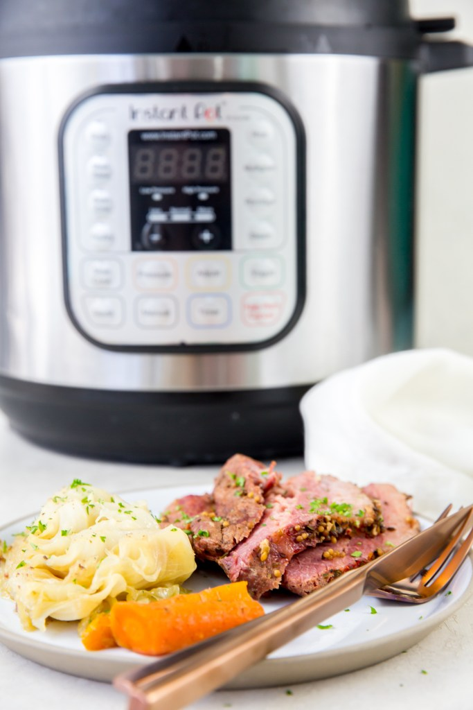 vertical image of corned beef, cabbage and carrots on a white plate with rose-colored fork and knee with napkin with an Instant Pot in the background