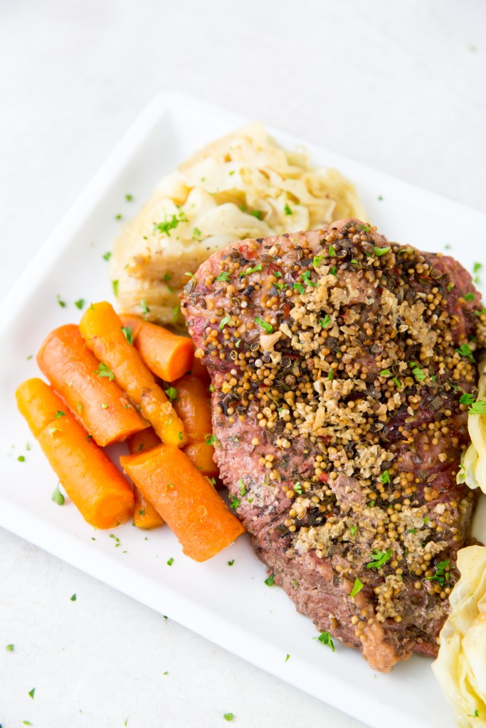 vertical image of corned beef, cabbage and carrots on a white plate