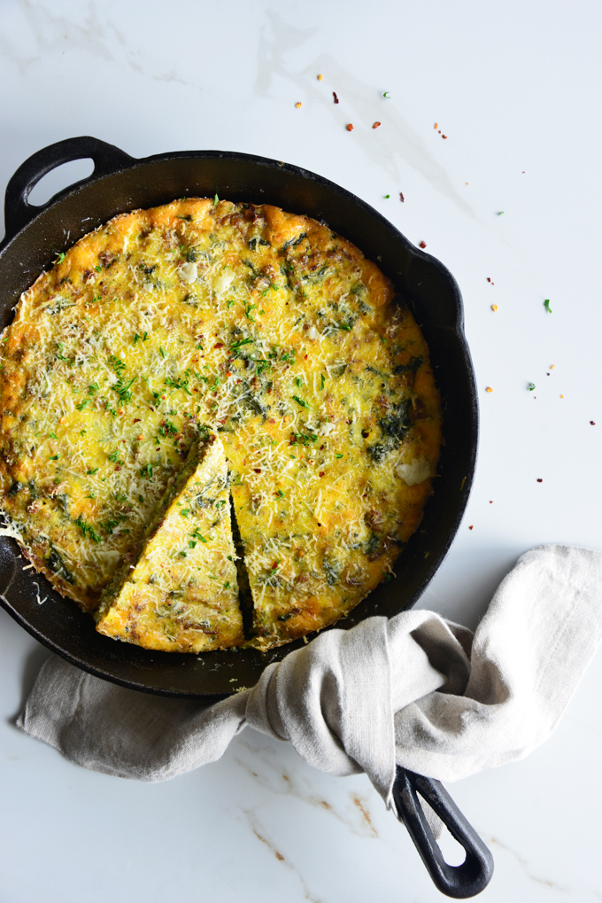 vertical image of a baked frittata in a cast iron skillet close up with a white fabric napkin