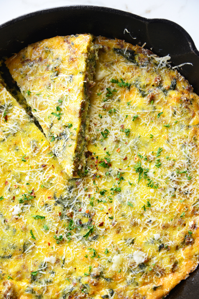 vertical image of a baked frittata in a cast iron skillet close up