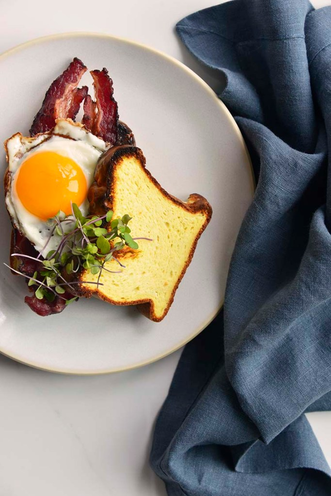 keto breakfast sandwich on a white plate with a blue napkin