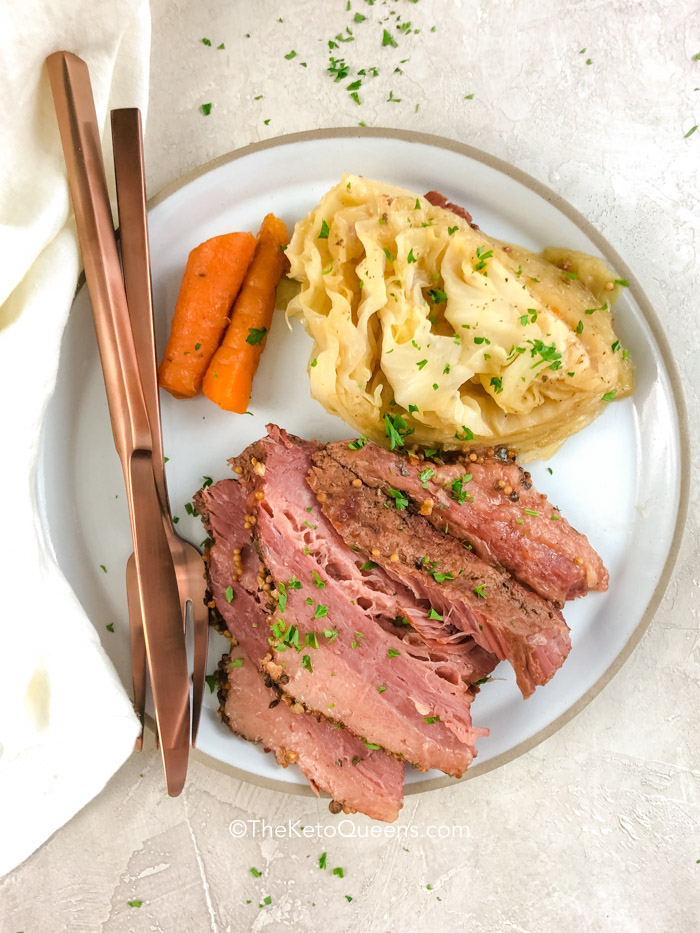 a plate of corned beef, cabbage and carrots