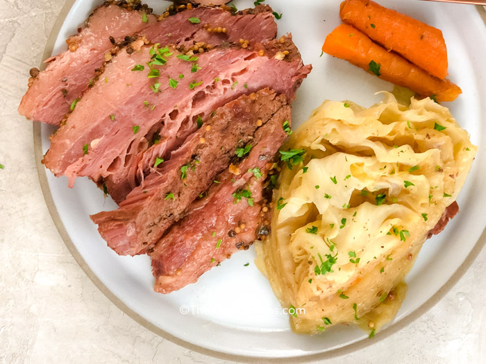 a plate of corned beef and cabbage with a fork and knife