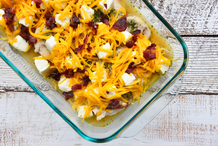 half baked chicken topped with cream cheese cubes and shredded cheese in a glass baking dish