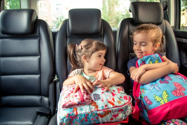 Children in the car go to school, happy, sweet faces of sisters